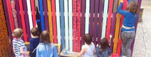 Kinder der FSX streichen eine Schuppenwand kunterbunt