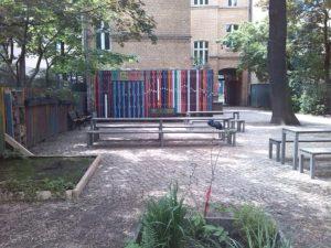 Blick auf den Schulhof der Freien Schule Kreuzberg mit Sitzbänken unter Bäumen, Beeten, einem bunt gestrichenen Schuppen und dem Schulgebäude, einem Altbau mit hellem Klinker aus der Kaiserzeit.