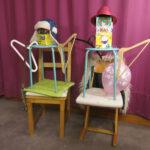 Stubenhockerskulpturen: Zwei lose anthropomorphe Figuren aus Stühlen, Hockern, Kleiderbügeln, Kartons, eine mit blauer Wintermütze, die andere mit rotem Strohhut.