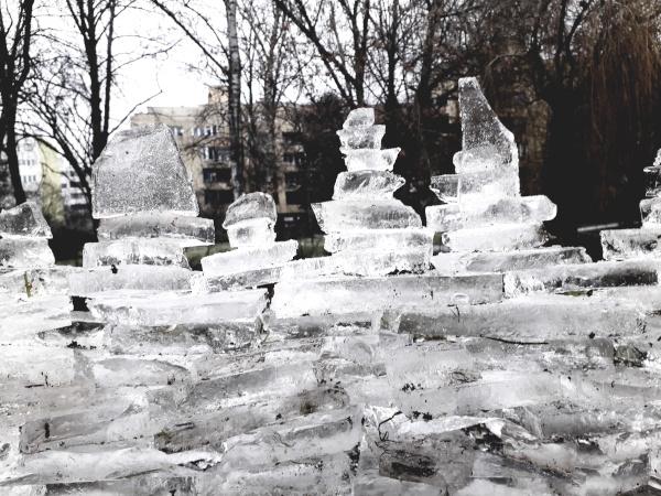 Durch klare Eiskulpturen schimmern graue Winterbäume im Hintergrund.